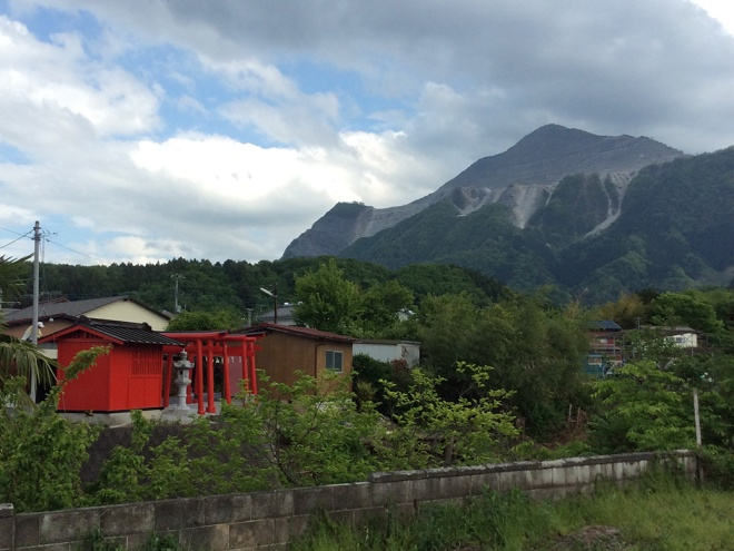 Mt. Buko and a bright red neighborhood shrine. The scarring at the top of Mt. Buko is a result of heavy mining of limestone used for the ever-present construction in the larger cities.