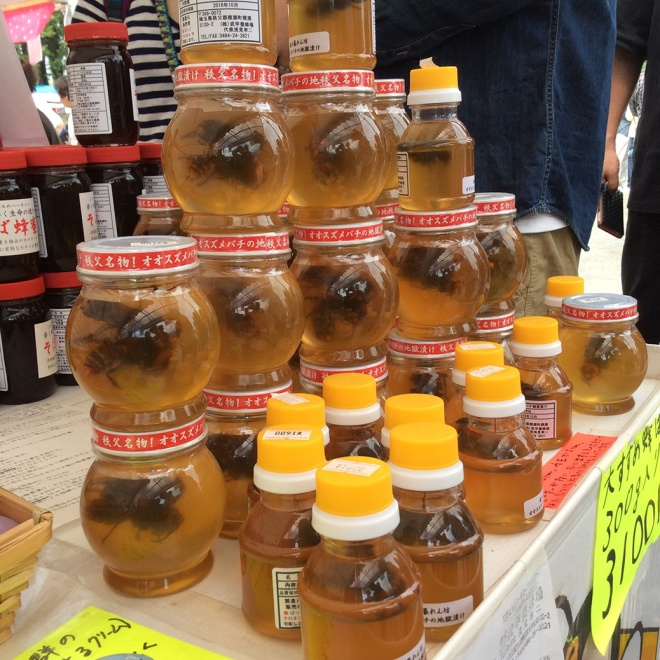 Local Chichibu honey for sale at Hitsujiyama Park. A very large queen bee is inside each jar.