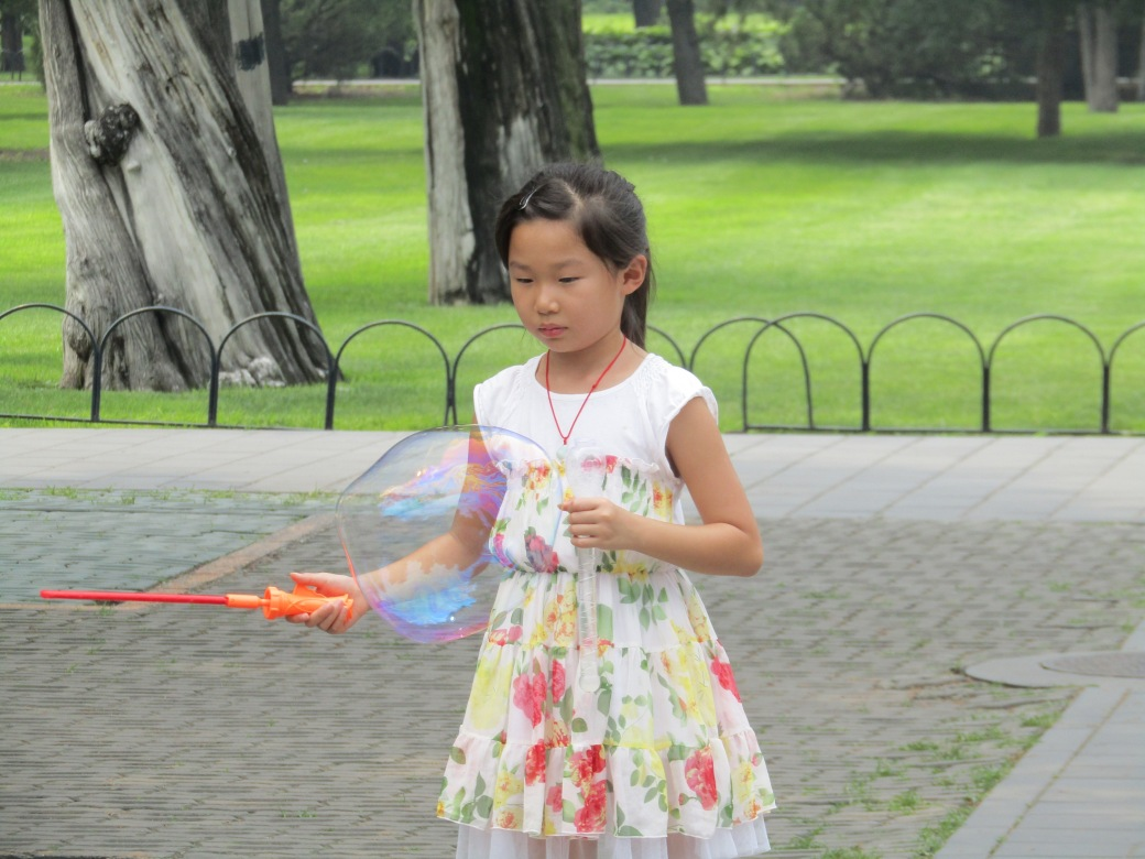 A girl filled the park with giant bubbles.