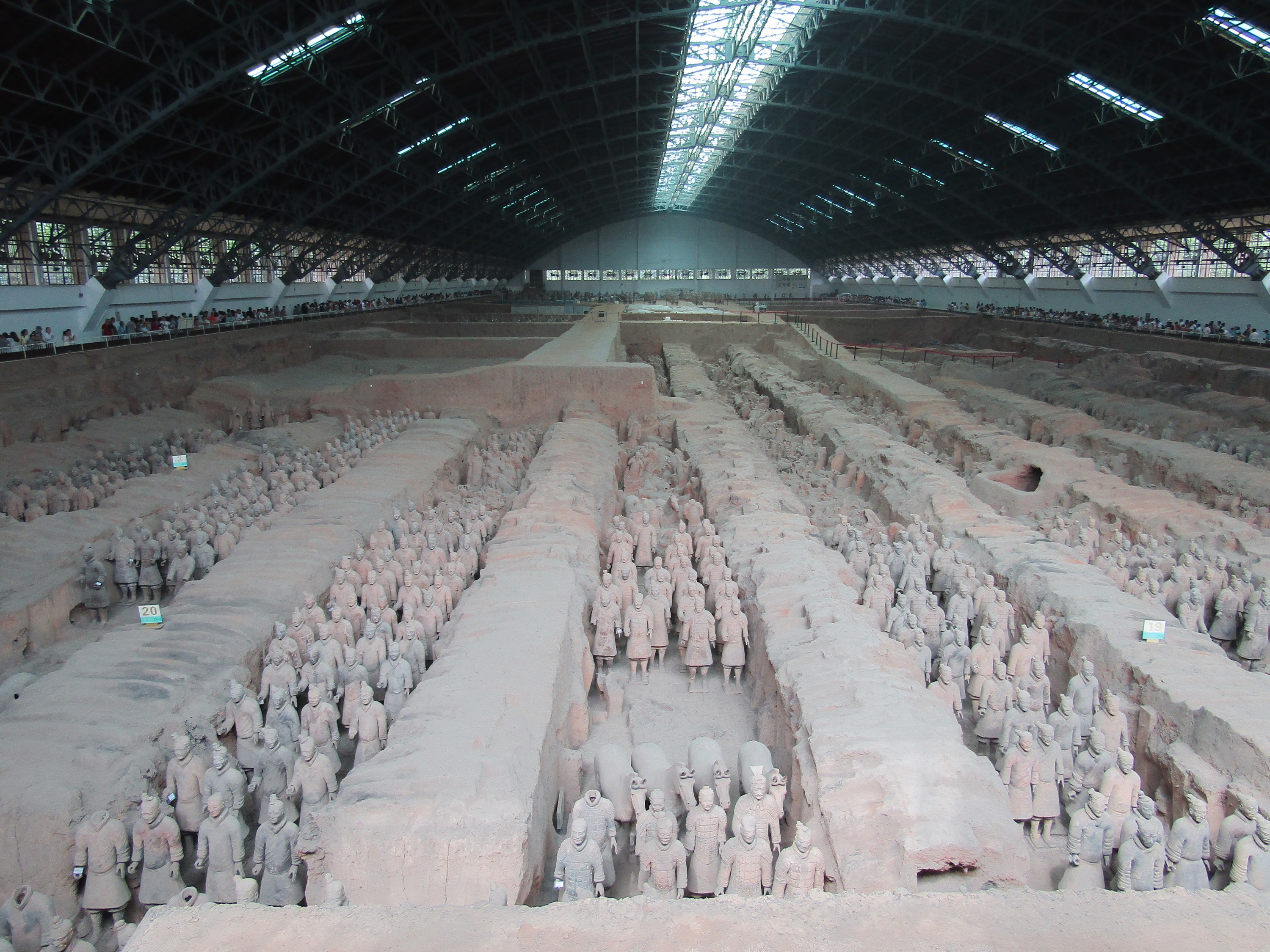 The terracotta army of Qin Shi Huang, the first emperor of China's first dynasty. He ordered the construction of the army during the third century B.C. to protect his tomb in the afterlife, but three years after his death, his empire was overthrown. The warriors were heavily damaged in the revolt and buried later as the wooden support beams rotted away. The army was rediscovered in 1974 by farmers who were digging a well.