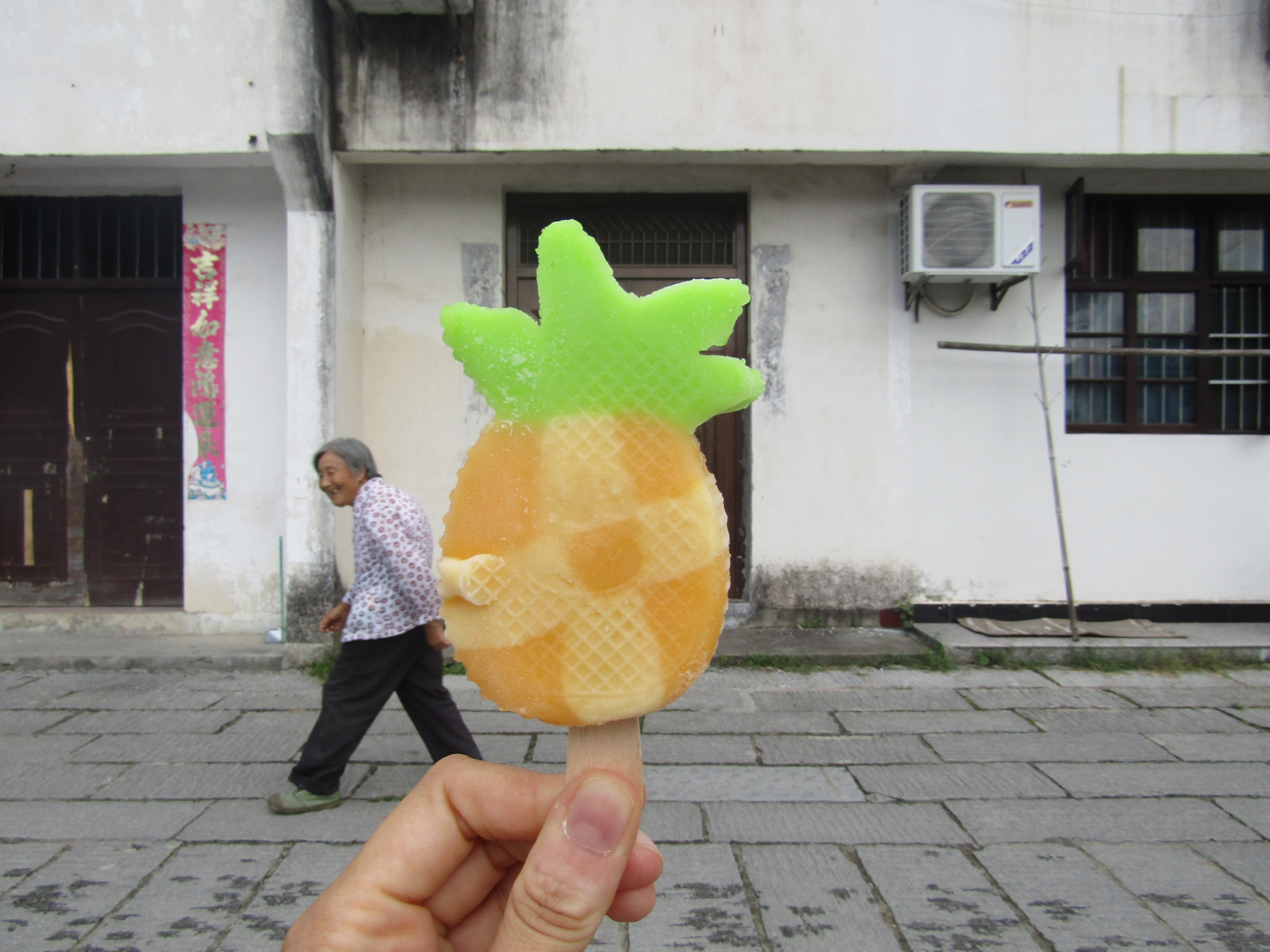 Nothing like a frozen treat on a hot and humid Chinese summer day. Viktoria snapped this photo of her pineapple pop as I caught the eye of the lady entering the background. She was really getting a kick out of the level of artistry going into the ice-sucker selfie.