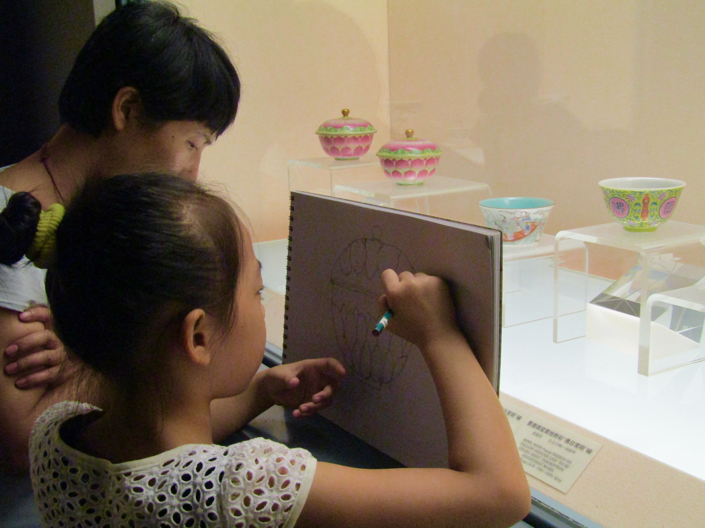At Shanghai Museum, a young artist sketches on of the Qing-era bowls on display.