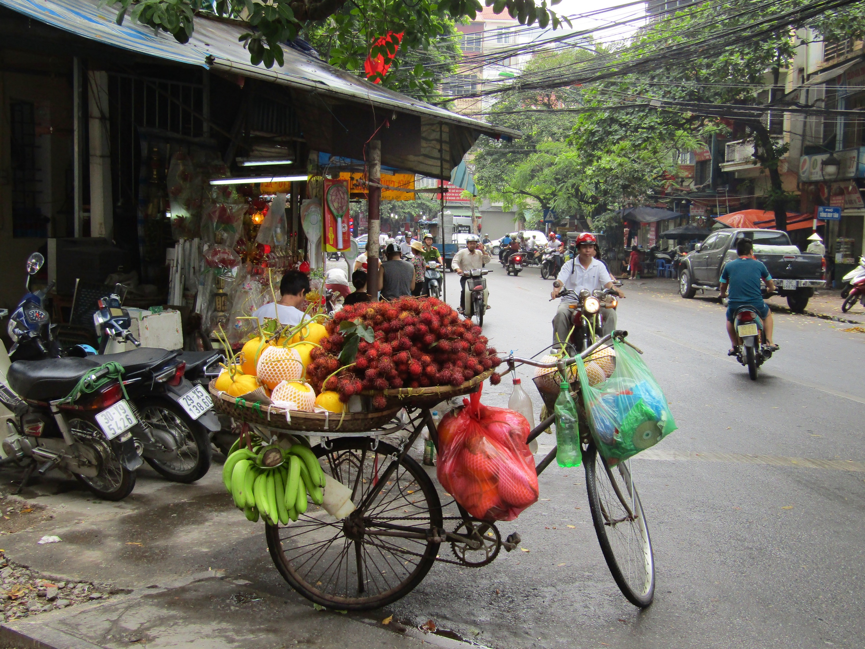 A parked bicycle is transformed into a fruit stand on a sidewalk on the outskirts of the Old Quarter shops.