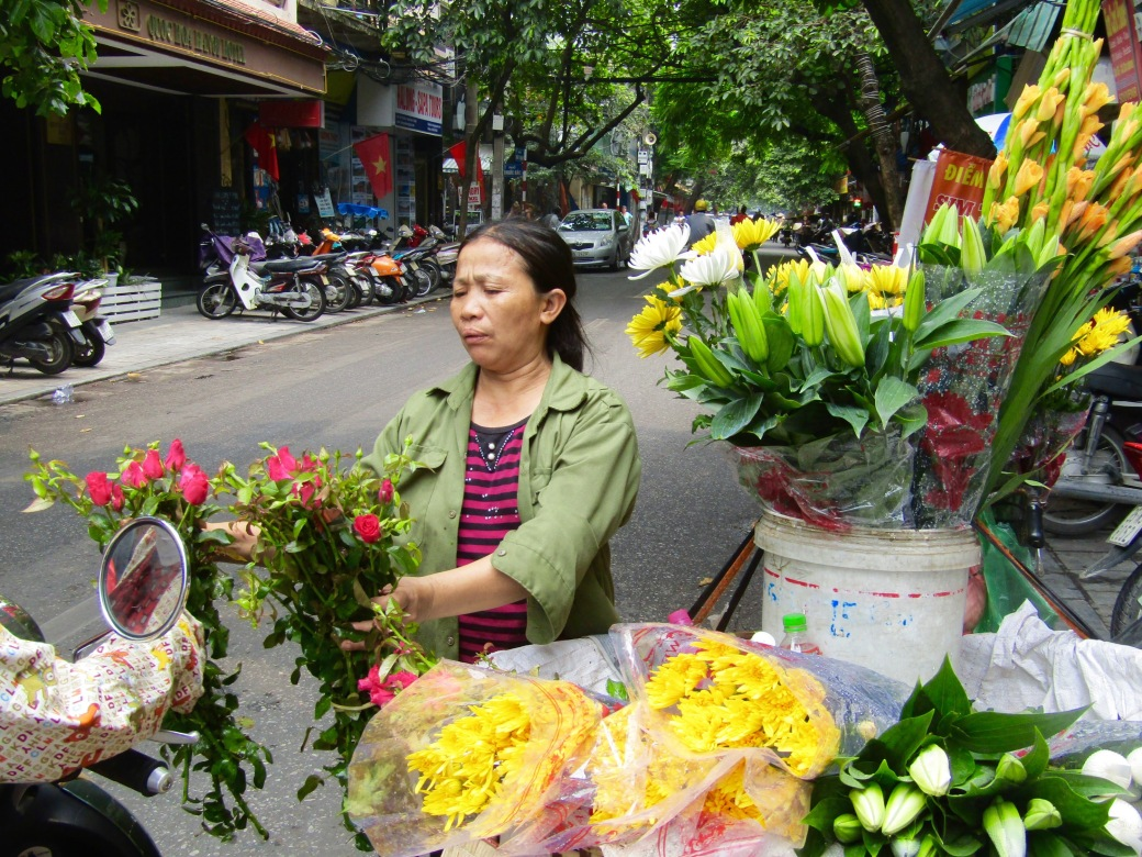 A flower vendor sizes up a pair of bouquets for a customer on the ever-present scooter