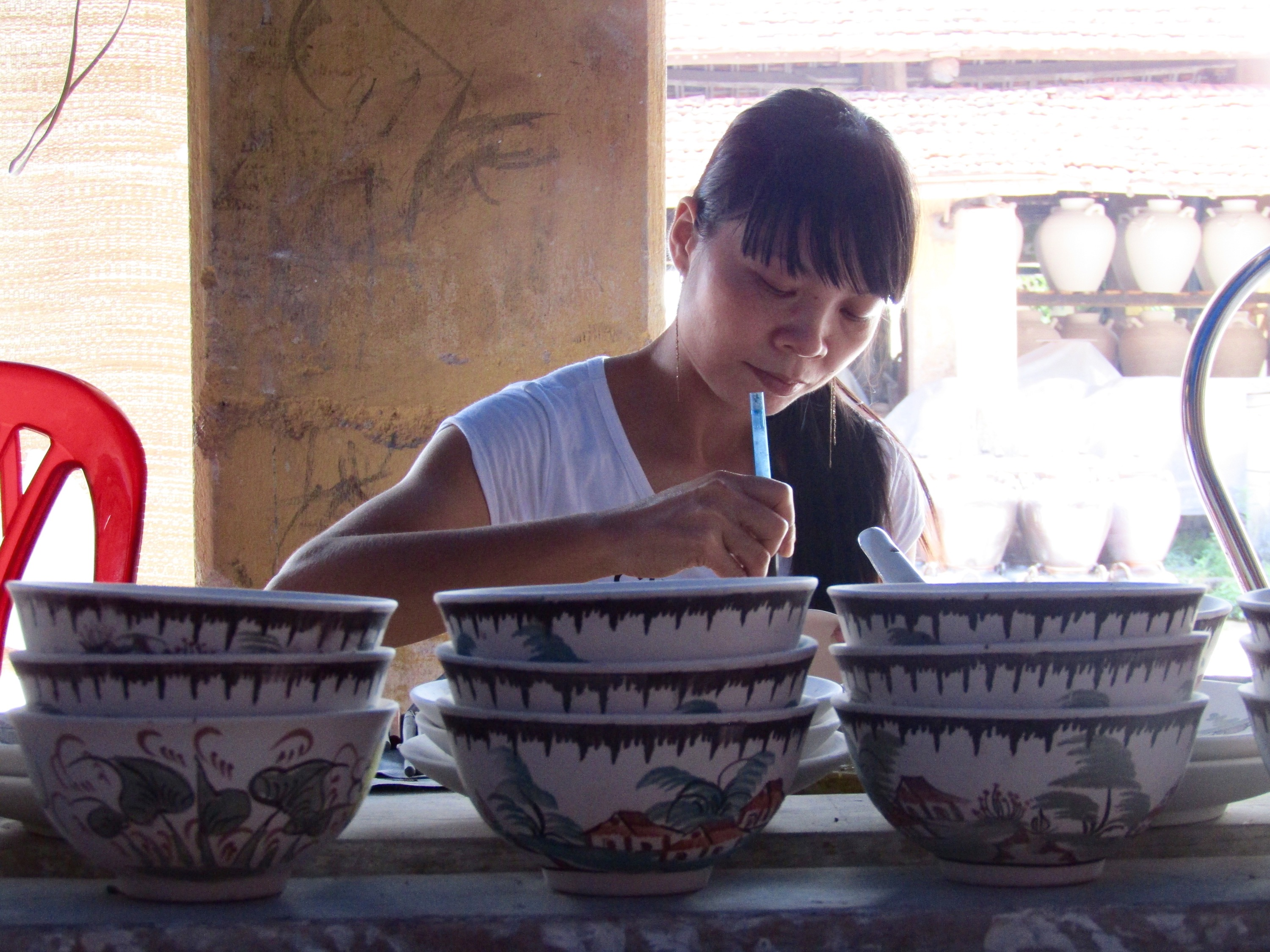 Inside, a woman puts the finishing touches on one of the ceramic bowls. She worked quickly and precisely, creating a unique scene on each piece.