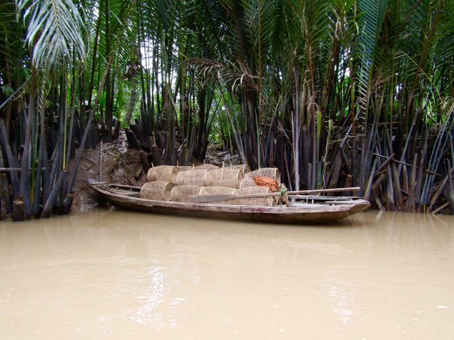 A boat full of bamboo fish traps parked along the shore of a creek. Nearly 60 percent of Vietnam's fishing output and a quarter of its agricultural land is located in the Mekong Delta.