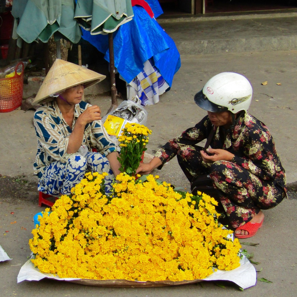 A typical transaction in Dong Ba Market between a vendor in a nón lá (conical hat) and a scooter rider.