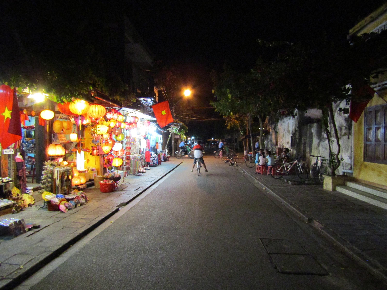 A boy on a bike coasts through the lantern-lit streets.