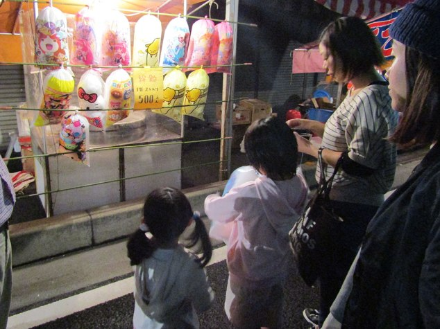 The kids buy their second bag of cotton candy of the night. Festival time is a time for letting loose.