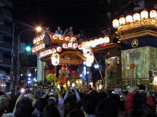 """Two of the massive floats meet in the middle of the road, stopping to """"battle"""" each other with music and dance. The float on the right won this particular battle."""