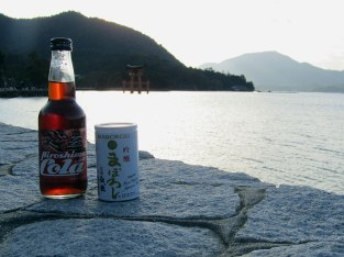 Enjoying a Hiroshima Cola and Maboroshi Sake as the sun sets behind the Great Torii on Miyajima. The unique natural cola is made with hassaku, a fruit similar to an orange or grapefruit.