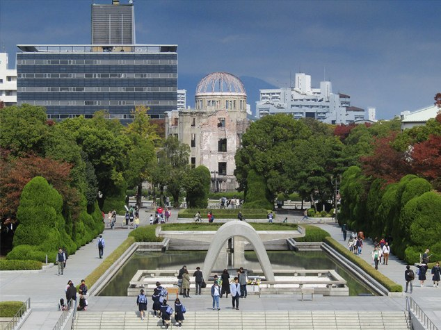 Hiroshima Peace Memorial Park as seen from the Peace Memorial Museum. The Memorial Cenotaph and Flame of Peace can be seen in the foreground. The Atomic Bomb Dome is in the distance.