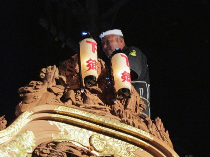 A man sitting atop the float while it's leaning to and fro...