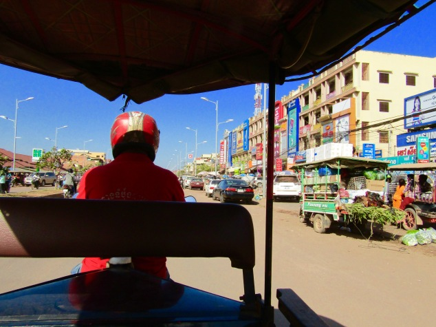 Riding into the city center in the back of a remork. Known as tuk-tuks in most of Southeast Asia, the Cambodian version is a cart pulled by a small motorbike or scooter.
