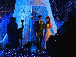 A couple poses for wedding photos at Caretta Shiodome's Canyon d'Azur light display