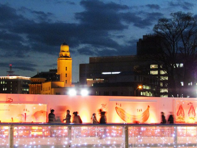Friday night family fun at the Red Brick Warehouse ice skating rink. The tower of the Yokohama Customs Museum is illuminated in the background.
