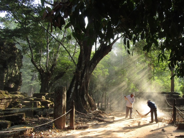 Workers clear fallen leaves from the path, kicking up a cloud of dust that caught the rays of the morning sun.