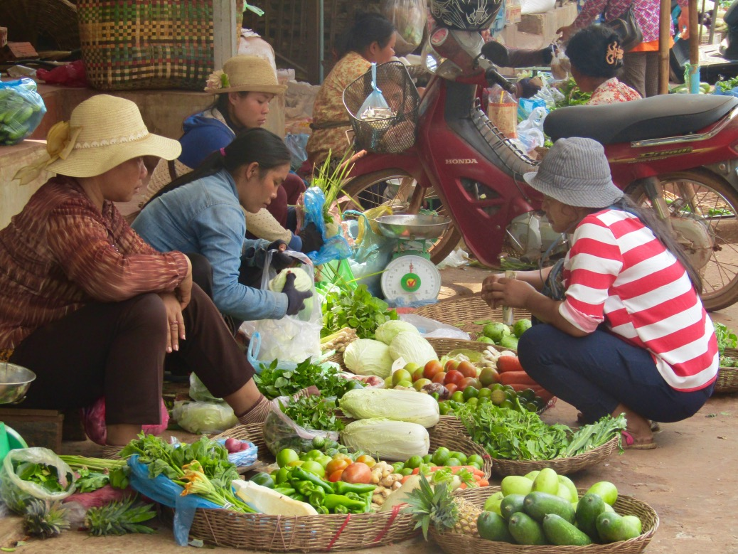 A group of vegetable vendors prepare an order for a customer.