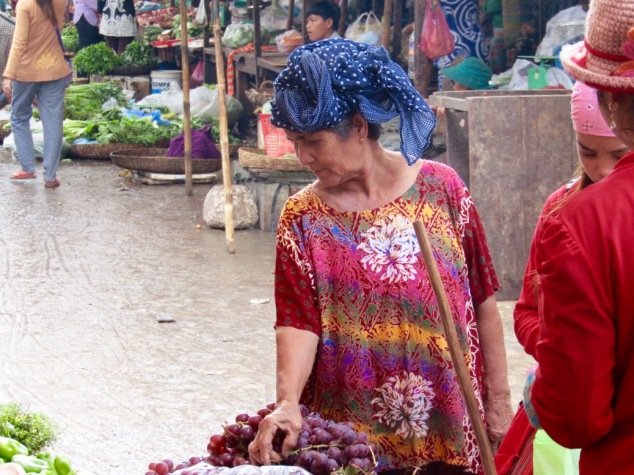 A market-goer inspects a large vine of grapes.