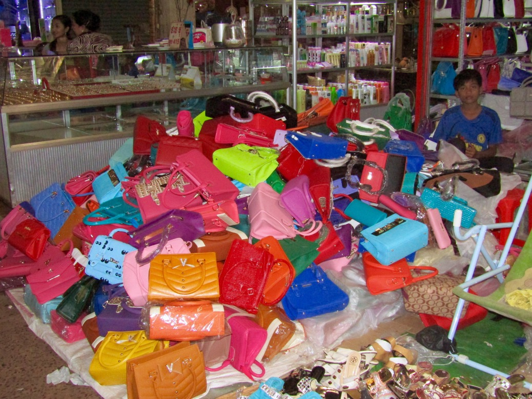 A boy mans a booth selling a literal mountain of purses. Most of the stalls were well organized, but a couple just piled their wares for all to see.