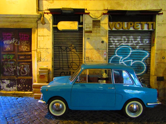 A restored Italian coupe parked in an alley in the Trastevere neighborhood. The district retained its distinct old world charm due in part to its separation from the rest of Rome by the Tiber River.