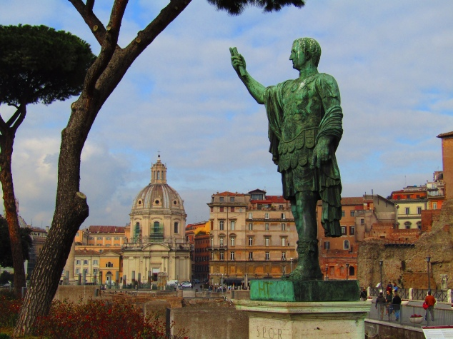 A statue of Caesar stands along the ruins of the Trajan Forum. The dome of Santa Maria di Loreto, a 16th-century Catholic church, stands in the background.