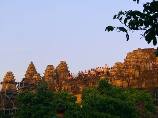 Tourists crowd the platform of Phnom Bakheng to wait for the sunset and a view of Angkor Wat.