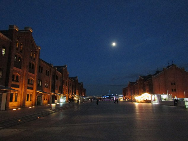 The blue lights of the Yokohama Bay Bridge deep in the background of the Red Brick Warehouse