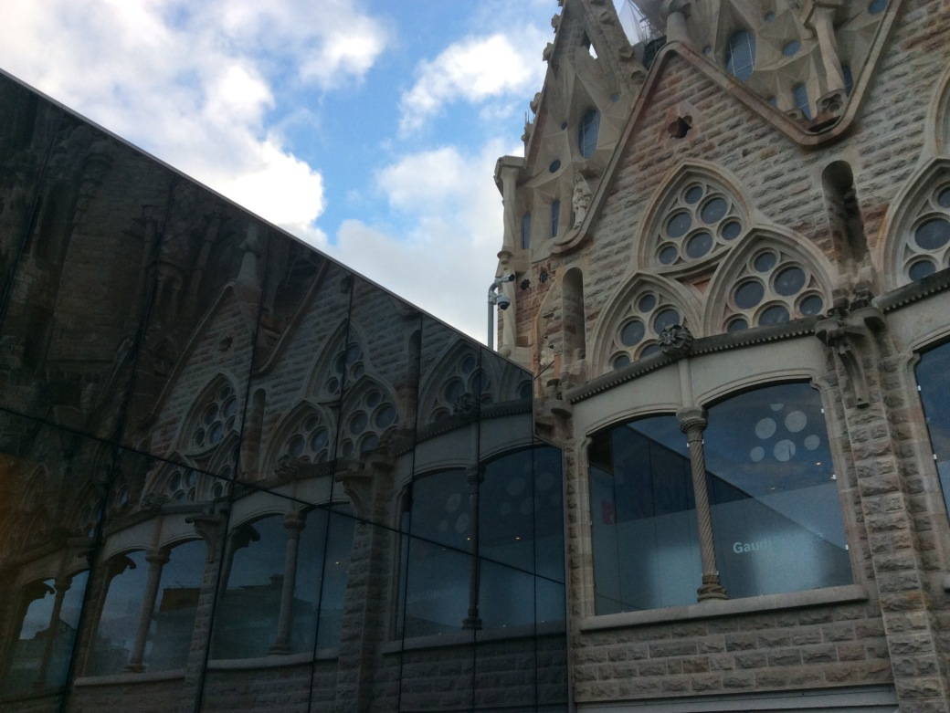 Outside, the neo-gothic cathedral reflects in the windows of the modern souvenir shop.