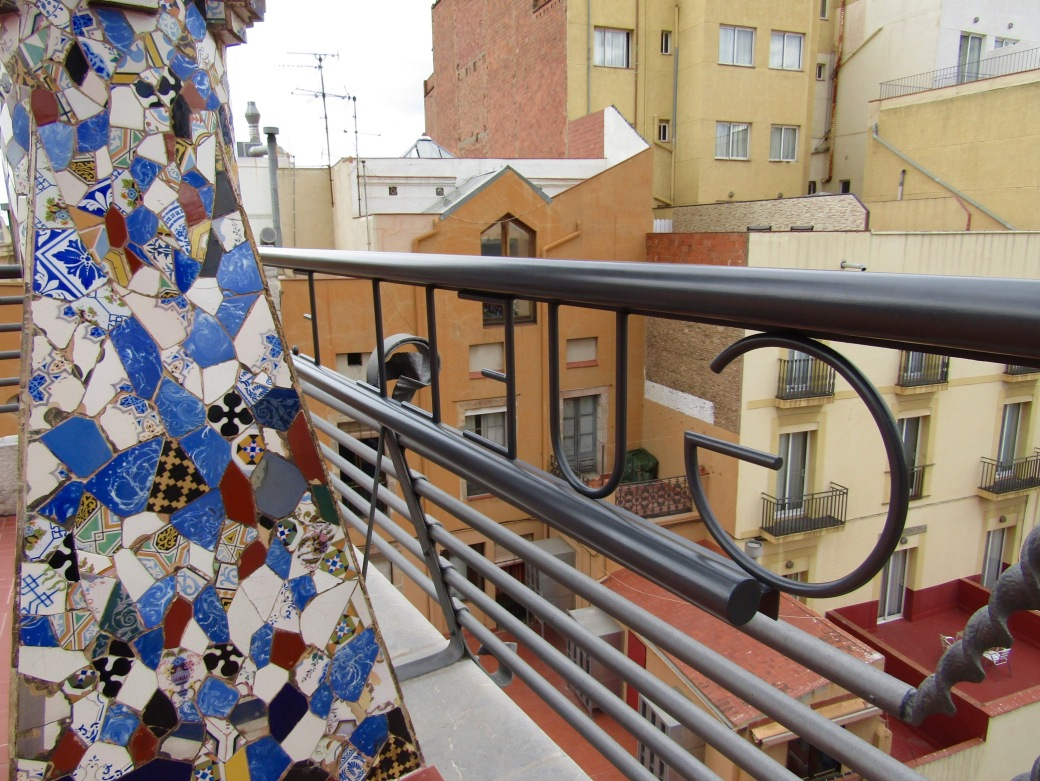 The roof of Palau Güell with mosaic tile work on the chimney and the Güell name written in ironwork on the rail.