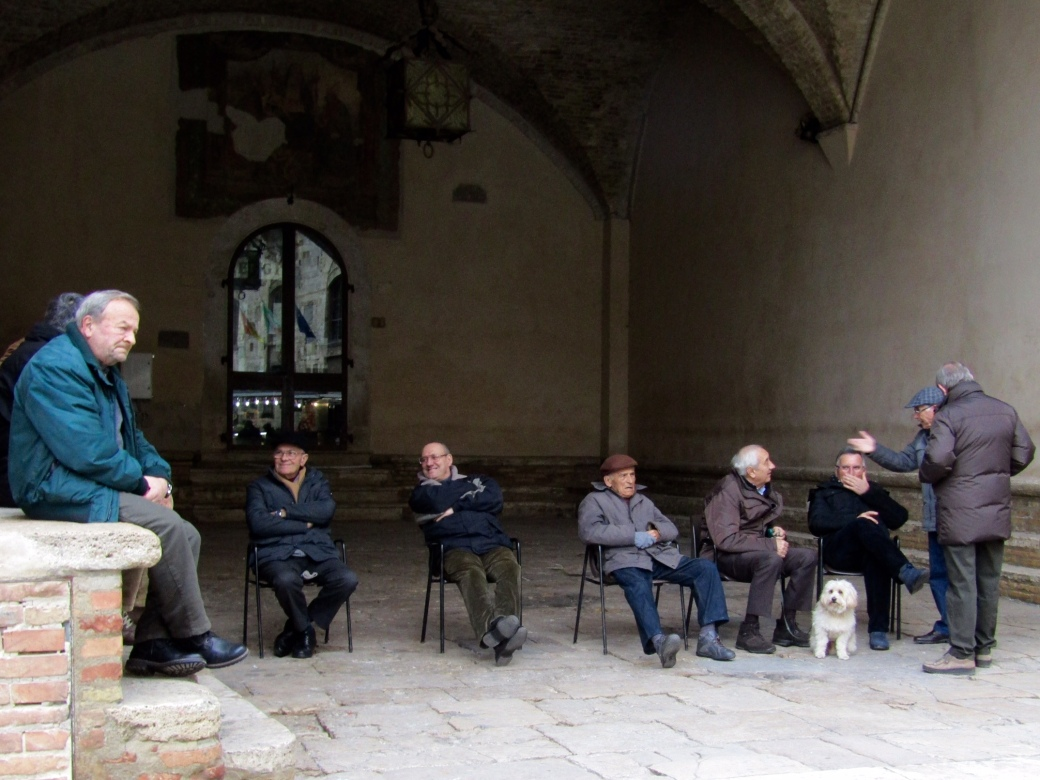 A group of locals gathered in San Gimignano's town square to chat and watch the tourists go by.