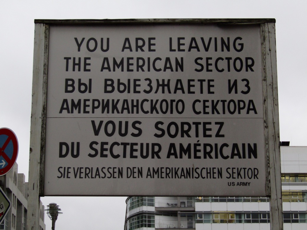 "The famous sign at Checkpoint Charlie, an original border crossing between East and West Berlin is now in a museum. The checkpoint has been recreated in its original spot, complete with ""American"" soldiers as a tourist photo op."