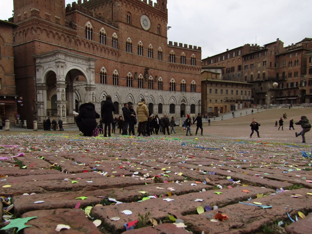Confetti and silly string color Siena's Piazza del Campo.