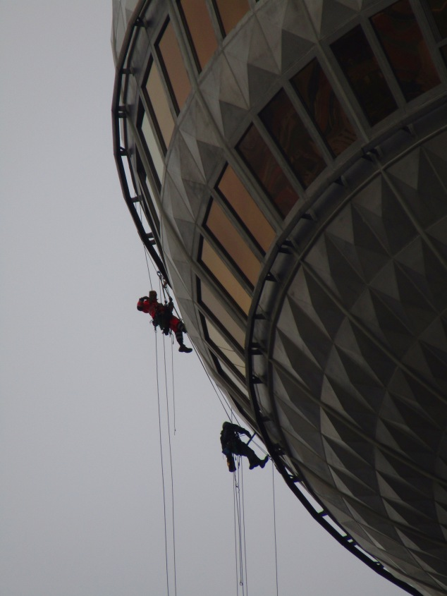 Climbers descending the sphere of the 1,200 foot tall TV tower in Berlin.