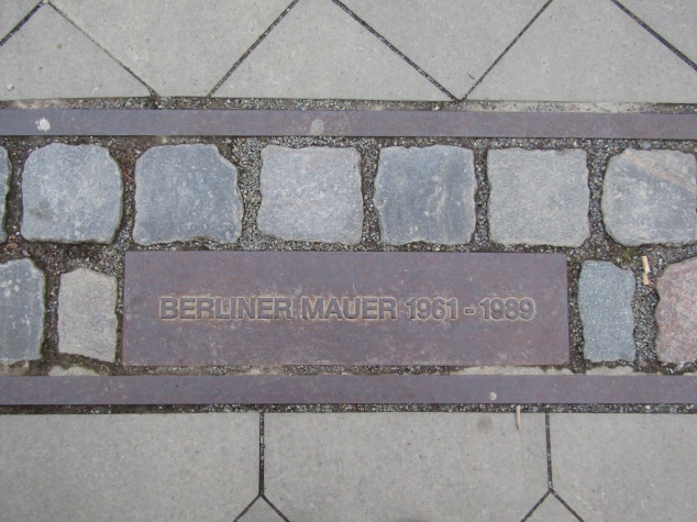 Very few pieces of the Berlin Wall remain today, but the path of the wall is still clearly marked by a double row of cobblestones with a plaque inserted at regular intervals.