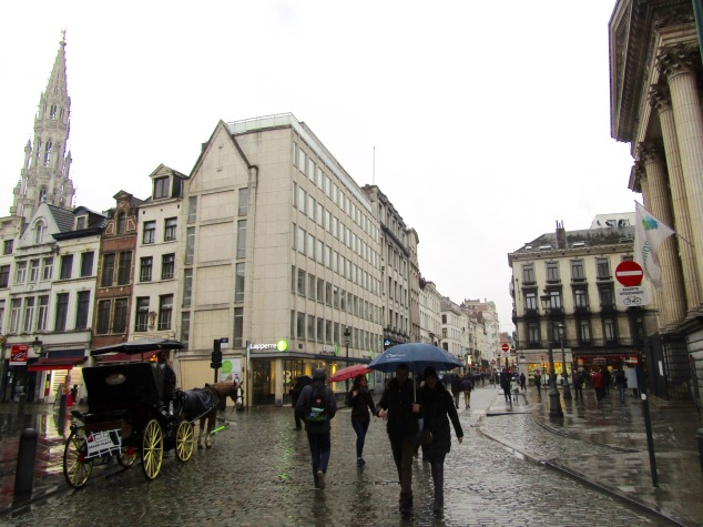 The rainy streets of Brussels. The tower of the Town Hall in Grand Place can be seen at the left.