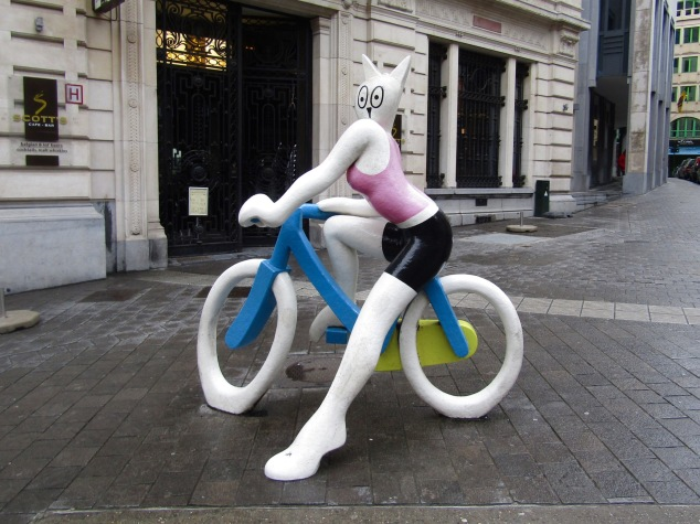 "A statue called ""La Cycliste"" by Alain Séchas features a cat on a bicycle overlooking a traffic intersection."