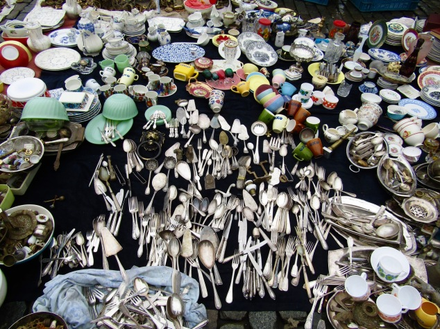 A vendor selling silverware and dishes at the Place du Jeu de Balle flea market. An argument broke out nearby after a customer stepped on and broke a plate then pretended she didn't do it.