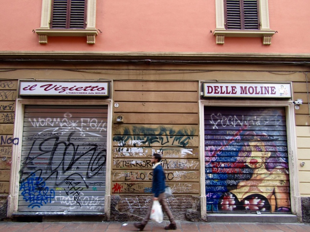Graffiti on storefronts near the University of Bologna campus.