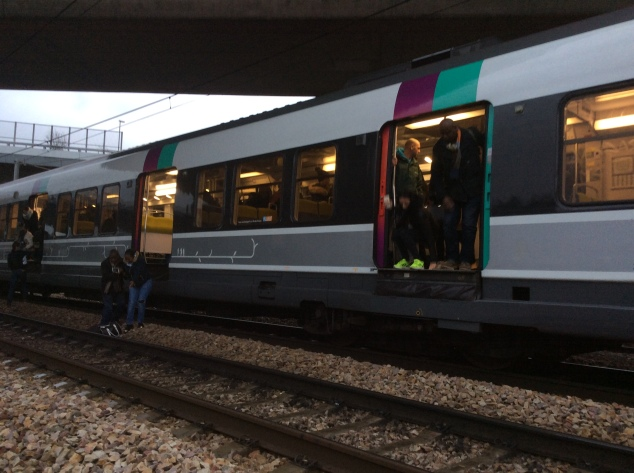 Passengers making the few foot jump from the train to the tracks below, most packing luggage from the airport.