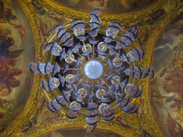 Looking up at the chandelier of the War Salon. The murals on the ceiling illustrate centuries of French military conquests.