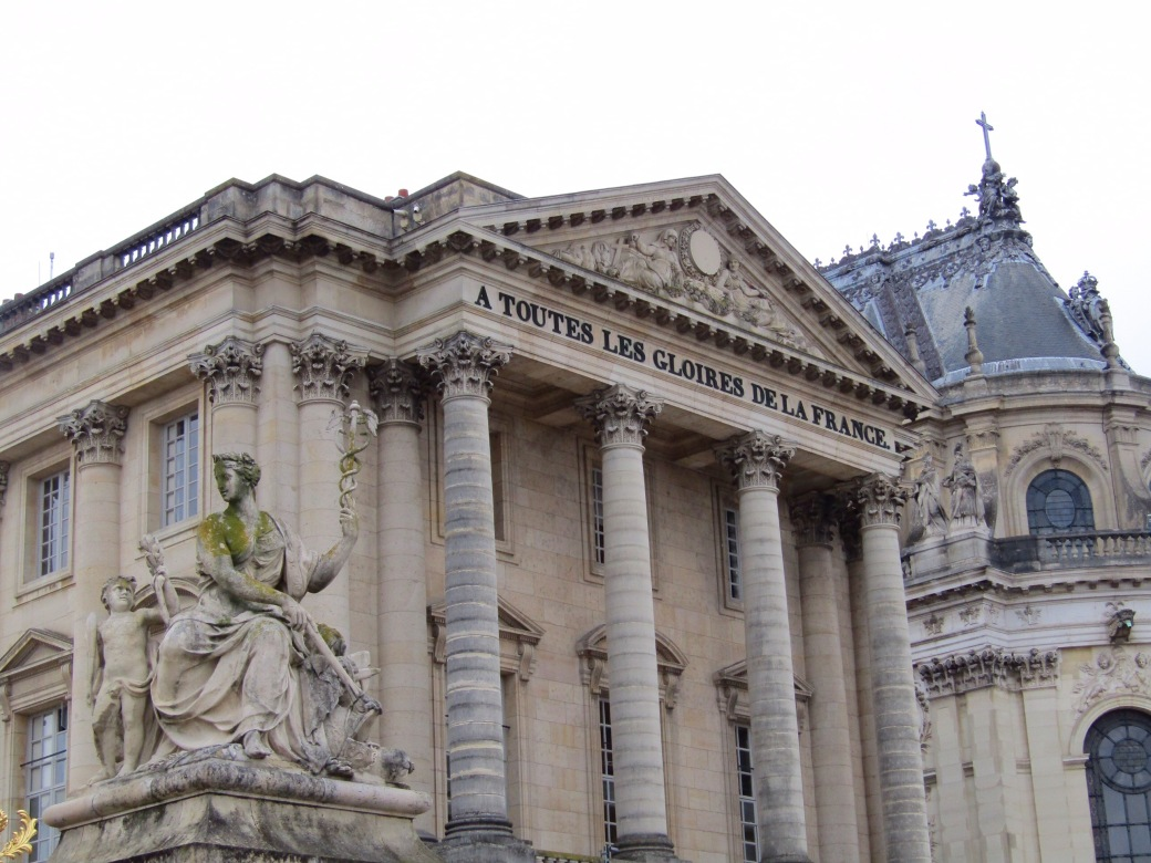 "Twin columned buildings stand on both sides of the courtyard at the palace's entrance. The inscription reads ""To All the Glories of France,"" added at the request of King Louis-Philippe when the palace was converted to a museum in 1830."