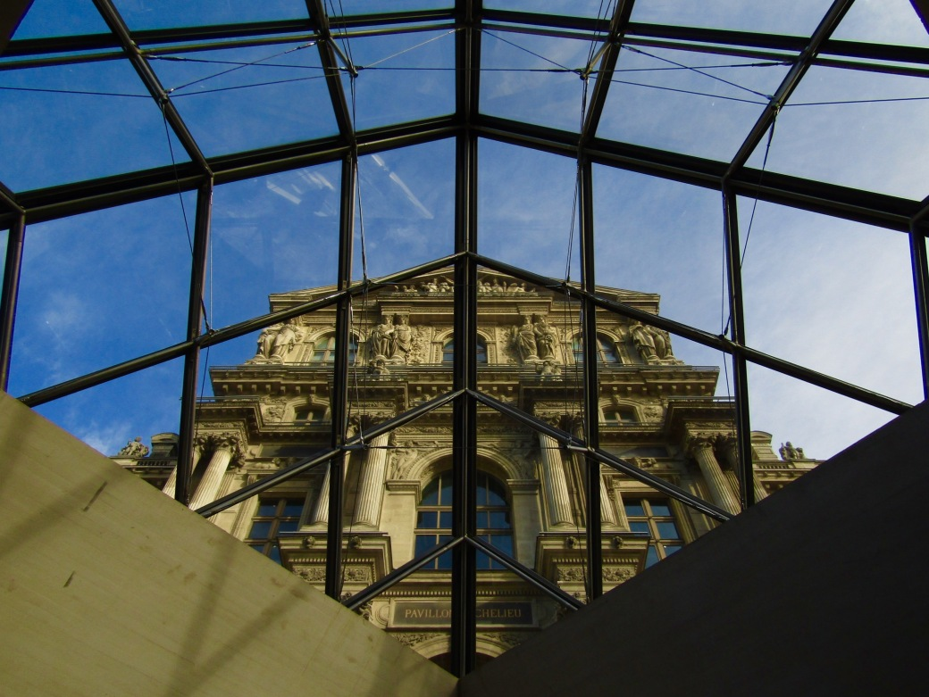 Looking up at the Louvre's Richelieu wing through the glass pyramid.