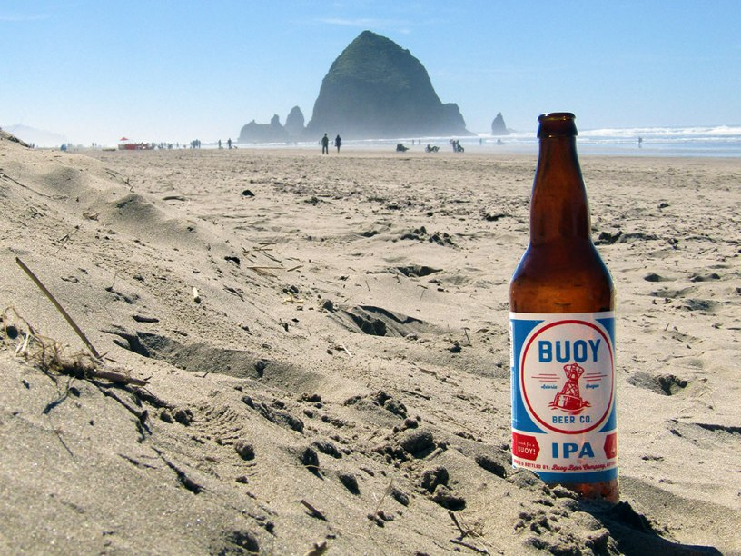 Buoy Beer Company IPA on Cannon Beach with Haystack Rock in the background.