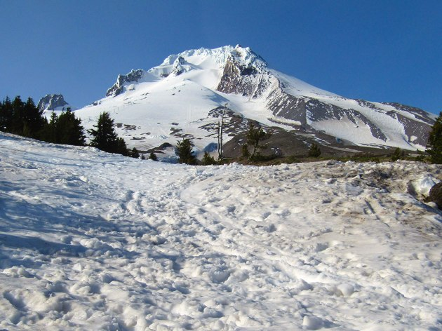 The snow-covered summit of Mount Hood begins to melt by early June.