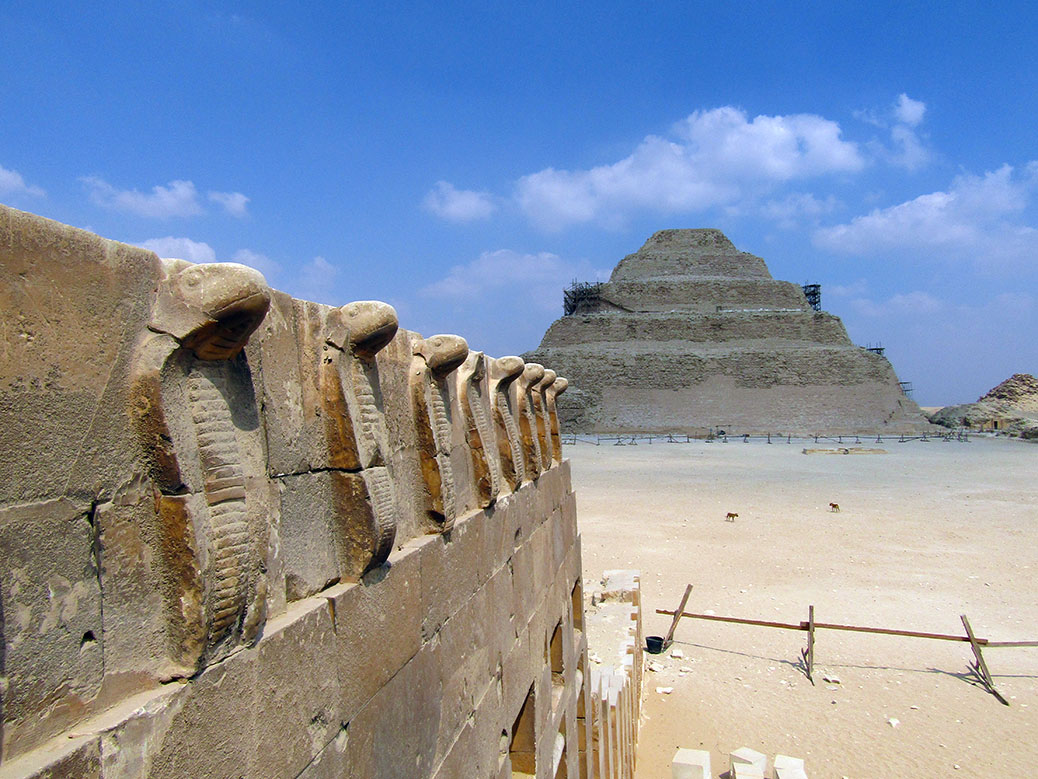 A line of Uraei (cobra) with the Pyramid of Djoser behind it.