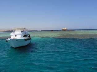 A boat sits waiting for snorkelers and divers to finish exploring.