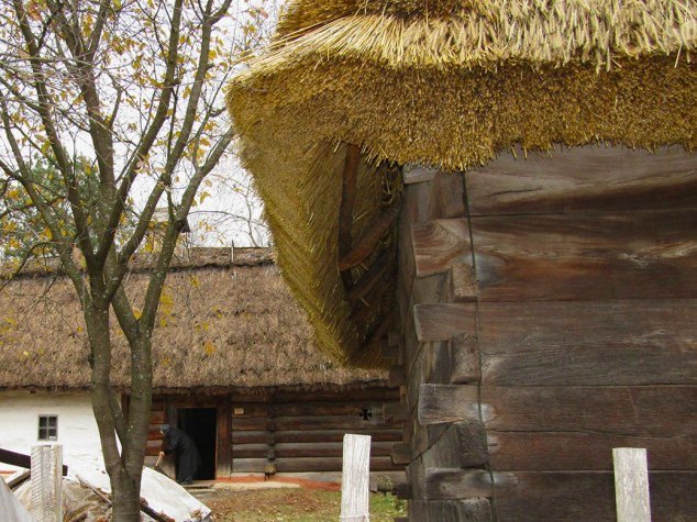 A caretaker sweeps the front of one of the village homes. This one had a fresh wheat thatched roof.